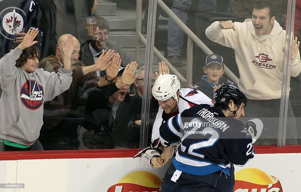 <a gi-track='captionPersonalityLinkClicked' href=/galleries/search?phrase=Chris+Thorburn&family=editorial&specificpeople=2222066 ng-click='$event.stopPropagation()'>Chris Thorburn</a> #22 of the Winnipeg Jets and <a gi-track='captionPersonalityLinkClicked' href=/galleries/search?phrase=John+Erskine&family=editorial&specificpeople=215268 ng-click='$event.stopPropagation()'>John Erskine</a> #4 of the Washington Capitals fight while fans react in NHL action at the MTS Centre on November 17, 2011 in Winnipeg, Manitoba, Canada.