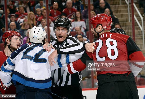 Chris Thorburn of the Winnipeg Jets and John Scott of the Arizona Coyotes are seperated by linesman Shane Heyer during the third period at Gila River...