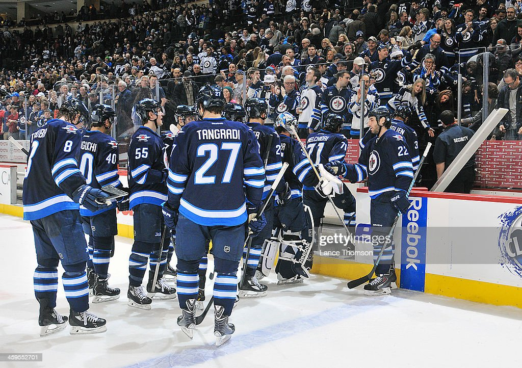 <a gi-track='captionPersonalityLinkClicked' href=/galleries/search?phrase=Chris+Thorburn&family=editorial&specificpeople=2222066 ng-click='$event.stopPropagation()'>Chris Thorburn</a> #22 of the Winnipeg Jets congratulates teammates as they leave the ice following a 6-4 victory over the Minnesota Wild at the MTS Centre on December 27, 2013 in Winnipeg, Manitoba, Canada.