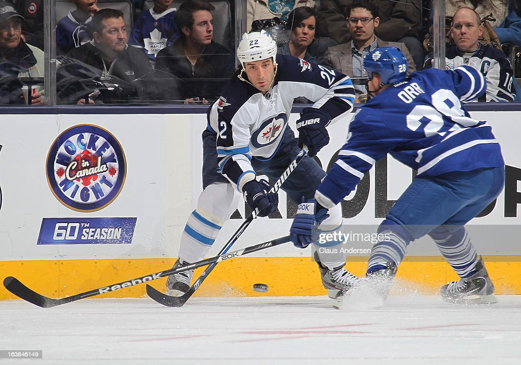 <a gi-track='captionPersonalityLinkClicked' href=/galleries/search?phrase=Chris+Thorburn&family=editorial&specificpeople=2222066 ng-click='$event.stopPropagation()'>Chris Thorburn</a> #22 of the Winnipeg Jets gets a puck past a checking <a gi-track='captionPersonalityLinkClicked' href=/galleries/search?phrase=Colton+Orr&family=editorial&specificpeople=581689 ng-click='$event.stopPropagation()'>Colton Orr</a> #28 of the Toronto Maple Leafs in a game on March 16, 2013 at the Air Canada Centre in Toronto, Ontario, Canada. The Jets defeated the Leafs 5-4 in an overtime shoot-out.