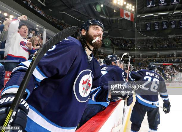 Chris Thorburn of the Winnipeg Jets is all smiles after celebrating a third period shorthanded goal against the Nashville Predators with teammate...