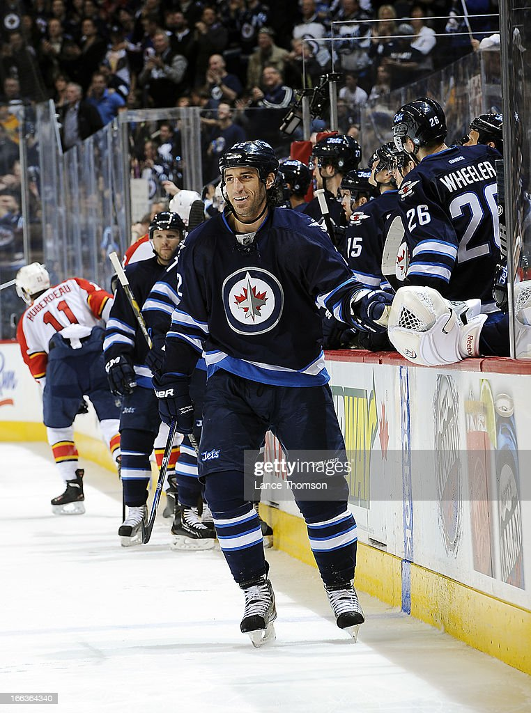 <a gi-track='captionPersonalityLinkClicked' href=/galleries/search?phrase=Chris+Thorburn&family=editorial&specificpeople=2222066 ng-click='$event.stopPropagation()'>Chris Thorburn</a> #22 of the Winnipeg Jets is all smiles as he celebrates his third period goal against the Florida Panthers with teammates at the bench at the MTS Centre on April 11, 2013 in Winnipeg, Manitoba, Canada.