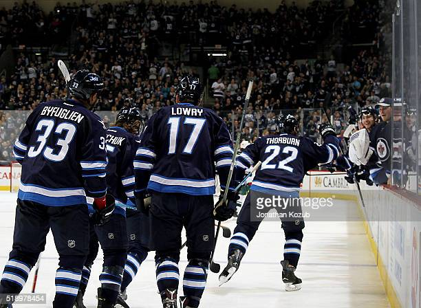 Chris Thorburn of the Winnipeg Jets leads the celebration of his second period goal against the Minnesota Wild with teammates at the bench at the MTS...