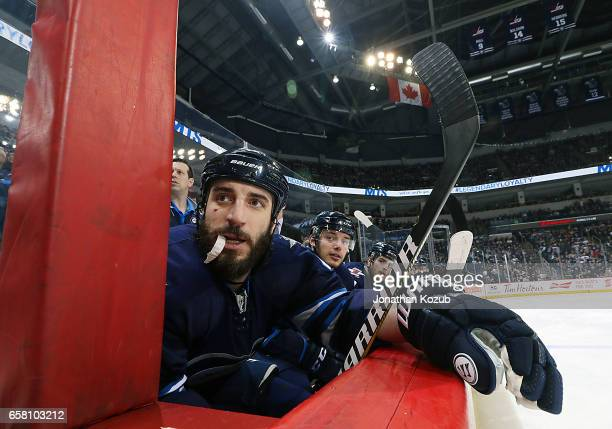 Chris Thorburn of the Winnipeg Jets looks on from the bench during first period action against the Vancouver Canucks at the MTS Centre on March 26...
