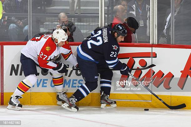 Chris Thorburn of the Winnipeg Jets plays the puck along the boards as Alex Kovalev of the Florida Panthers gives chase during first period action at...