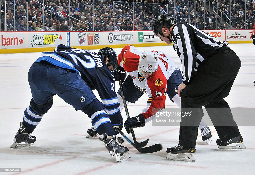 <a gi-track='captionPersonalityLinkClicked' href=/galleries/search?phrase=Chris+Thorburn&family=editorial&specificpeople=2222066 ng-click='$event.stopPropagation()'>Chris Thorburn</a> #22 of the Winnipeg Jets takes a third period face-off against <a gi-track='captionPersonalityLinkClicked' href=/galleries/search?phrase=Marcel+Goc&family=editorial&specificpeople=541626 ng-click='$event.stopPropagation()'>Marcel Goc</a> #57 of the Florida Panthers at the MTS Centre on December 20, 2013 in Winnipeg, Manitoba, Canada.