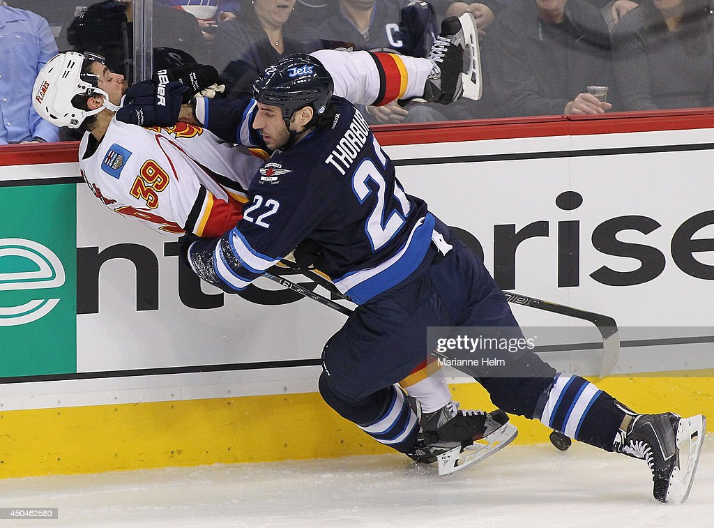 <a gi-track='captionPersonalityLinkClicked' href=/galleries/search?phrase=Chris+Thorburn&family=editorial&specificpeople=2222066 ng-click='$event.stopPropagation()'>Chris Thorburn</a> #22 of the Winnipeg Jets takes down TJ Galiardi #39 of the Calgary Flames in third period action in an NHL game at the MTS Centre on November 18, 2013 in Winnipeg, Manitoba, Canada.