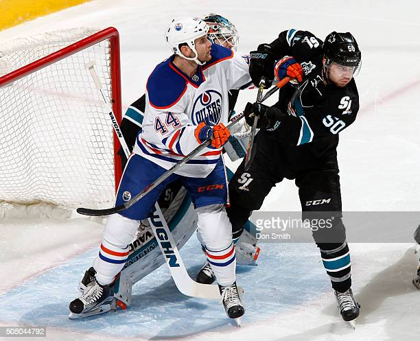 Chris Tierney of the San Jose Sharks defends the net against Zack Kassian of the Edmonton Oilers during a NHL game at the SAP Center at San Jose on...