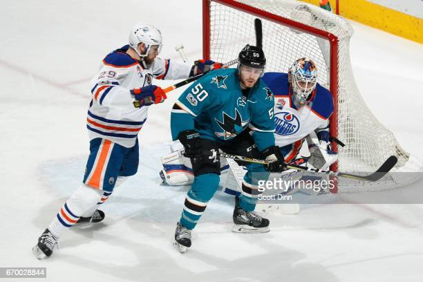 Chris Tierney of the San Jose Sharks is defended by Leon Draisaitl and Cam Talbot of the Edmonton Oilers in Game Four of the Western Conference First...