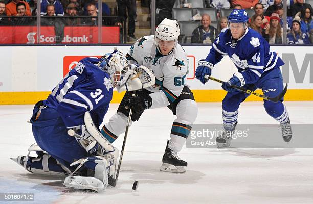 Chris Tierney of the San Jose Sharks is stopped in close by Garret Sparks of the Toronto Maple Leafs as teammate Morgan Rielly looks on during NHL...