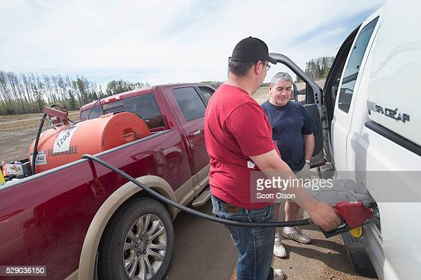 Chris Tronsgard tops off fuel for Mario Monreal as he hauls some of his possessions after evacuating his home on May 7 2016 in Fort McMurray Alberta...