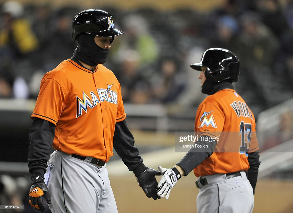 Chris Valaika #13 of the Miami Marlins congratulates teammate <a gi-track='captionPersonalityLinkClicked' href=/galleries/search?phrase=Giancarlo+Stanton&family=editorial&specificpeople=8983978 ng-click='$event.stopPropagation()'>Giancarlo Stanton</a> #27 on scoring against the against the Minnesota Twins during the fifth inning of the second game of a doubleheader on April 23, 2013 at Target Field in Minneapolis, Minnesota.