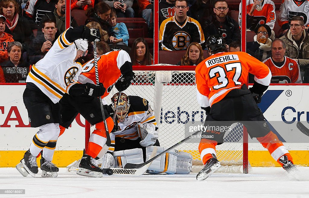 Chris VandeVelde and Jay Rosehill of the Philadelphia Flyers battle for the loose puck with goaltender Tuukka Rask and Torey Krug of the Boston...