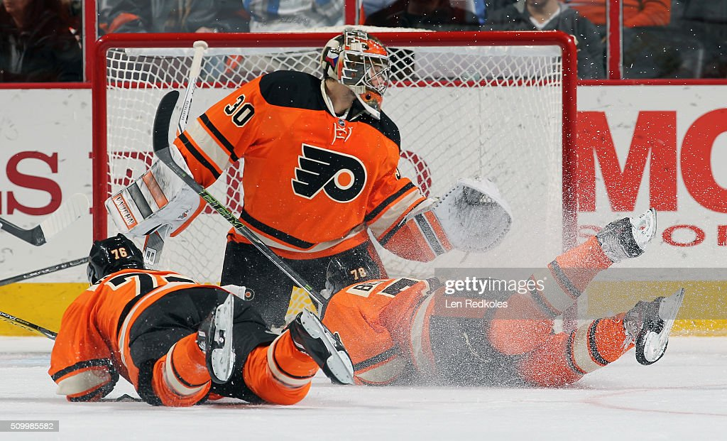Chris VandeVelde #76 and Pierre-Edouard Bellemare #78 of the Philadelphia Flyers dive in front of goaltender Michal Neuvirth #30 of the New Jersey Devils on February 13, 2016 at the Wells Fargo Center in Philadelphia, Pennsylvania.