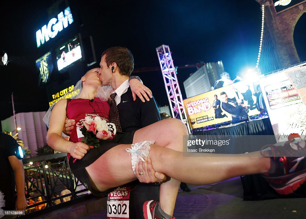 Chris Vogel plants a kiss on his wife Julie Nelson as they pause from running to renew their wedding vows during the Zappos.com Rock 'n' Roll Las Vegas Marathon & Half-Marathon on December 2, 2012 in Las Vegas, Nevada.