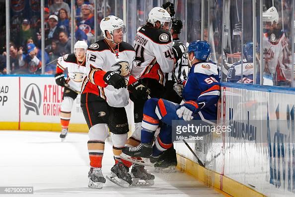 Chris Wagner of the Anaheim Ducks skates as teammate Nate Thompson checks Johnny Boychuk of the New York Islanders into the boards at Nassau Veterans...