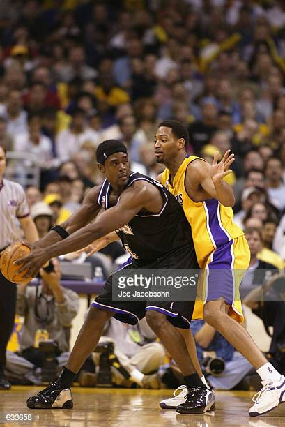 Chris Webber of the Sacramento Kings looks to pass around Robert Horry of the Los Angeles Lakers in Game four of the Western Conference Finals during...