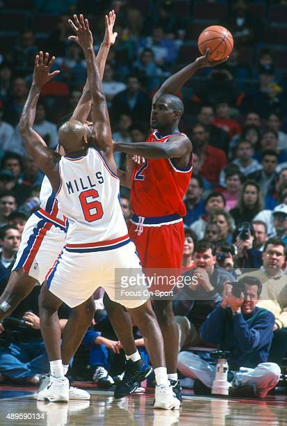 Chris Webber of the Washington Bullets looks to pass over the top of Terry Mills of the Detroit Pistons during an NBA Basketball game circa 1995 at...