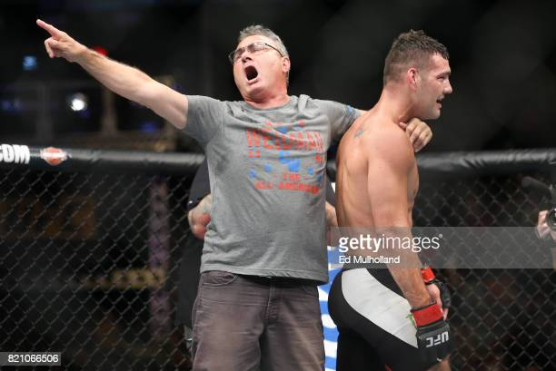 Chris Weidman and father Charlie Weidman celebrate Weidman's submission win during his UFC Fight Night middleweight bout at the Nassau Veterans...