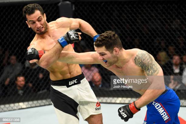 Chris Weidman lands a punch on Gegard Mousasi of the Netherlands in their middleweight bout during the UFC 210 event at KeyBank Center on April 8...