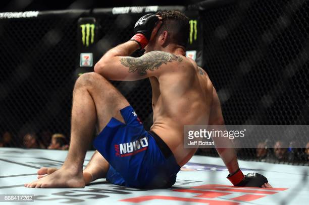 Chris Weidman sits on the Octagon after he took a knee to the head from Gegard Mousasi of the Netherlands during the UFC 210 event at the KeyBank...