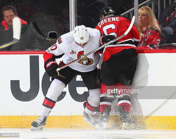 Chris Wideman of the Ottawa Senators and Andy Greene of the New Jersey Devils come together at the boards during the game at Prudential Center on...