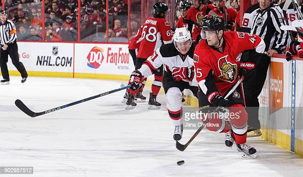 Chris Wideman of the Ottawa Senators carries the puck in as Sergey Kalinin of the New Jersey Devils skates after him at Canadian Tire Centre on...