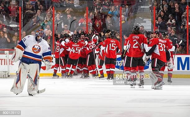 Chris Wideman of the Ottawa Senators celebrates an overtime win with teammates as Jaroslav Halak of the New York Islanders skates away at Canadian...
