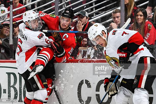 Chris Wideman of the Ottawa Senators checks Jonathan Toews of the Chicago Blackhawks into the glass as Kyle Turris watches the puck in the first...