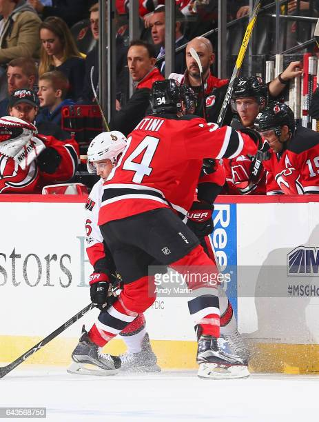 Chris Wideman of the Ottawa Senators is checked at the boards by Steven Santini of the New Jersey Devils during the game at Prudential Center on...