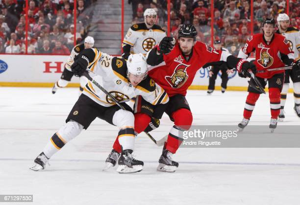 Chris Wideman of the Ottawa Senators is held up by Frank Vatrano of the Boston Bruins trying to get to a loose puck in Game Five of the Eastern...