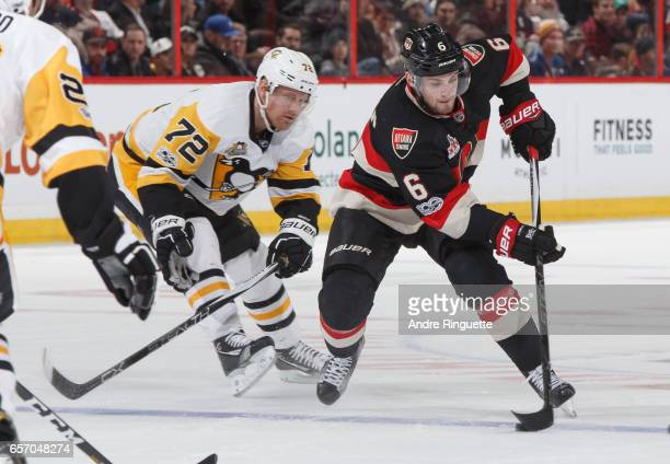Chris Wideman of the Ottawa Senators skates up ice with the puck against Patric Hornqvist of the Pittsburgh Penguins at Canadian Tire Centre on March...