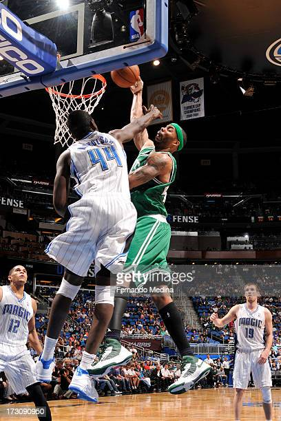 Chris Wilcox of the Boston Celtics dunks against Andrew Nicholson of the Orlando Magic on April 13 2013 at Amway Center in Orlando Florida NOTE TO...