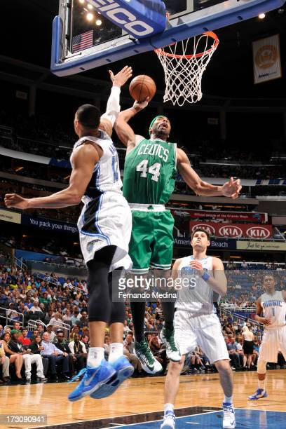 Chris Wilcox of the Boston Celtics dunks against Tobias Harris of the Orlando Magic on April 13 2013 at Amway Center in Orlando Florida NOTE TO USER...