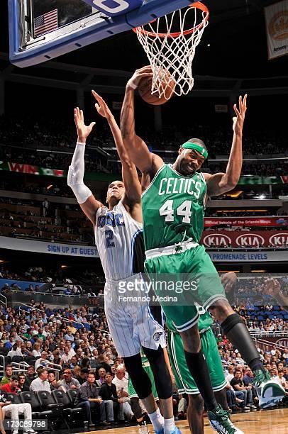 Chris Wilcox of the Boston Celtics grabs a rebound against Tobias Harris of the Orlando Magic on April 13 2013 at Amway Center in Orlando Florida...