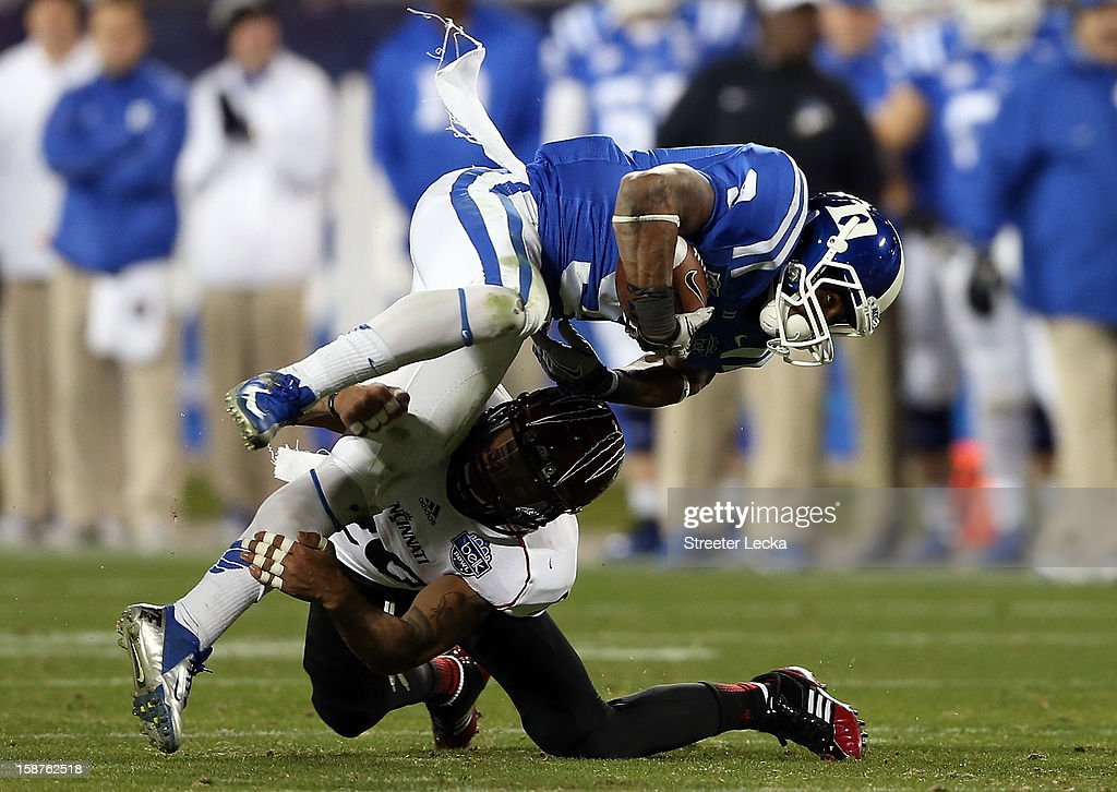 Chris Williams #20 of the Cincinnati Bearcats tackles Josh Snead #9 of the Duke Blue Devils during their game at Bank of America Stadium on December 27, 2012 in Charlotte, North Carolina.