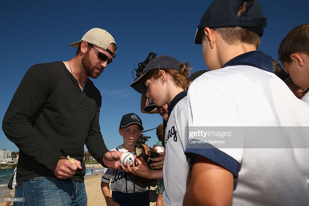 Chris Withrow of the Los Angeles Dodgers signs autographs for players from Illawong Little League during a Los Angeles Dodgers players visit at Bondi Beach on March 19, 2014 in Sydney, Australia.