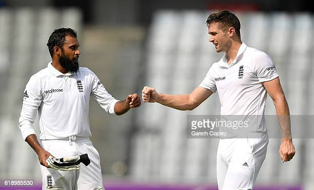 Chris Woakes and Adil Rashid of England punch gloves at drinks during the second day of the 2nd Test match between Bangladesh and England at...