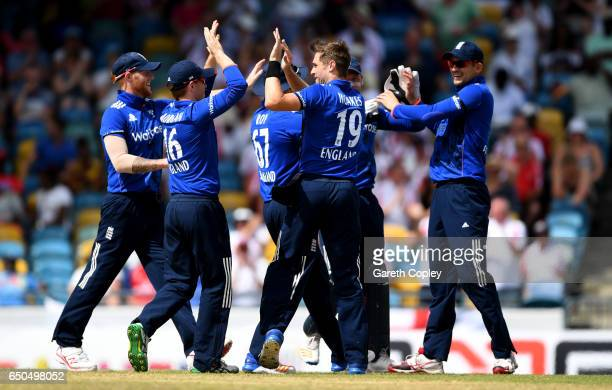 Chris Woakes of England celebrates with teammates after dismissing Kraigg Brathwaite of the West Indies during the 3rd One Day International between...