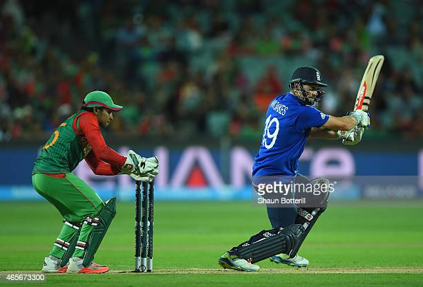 Chris Woakes of England plays a shot as Mushfiqur Rahim of Bangladesh looks on during the 2015 ICC Cricket World Cup match between England and...