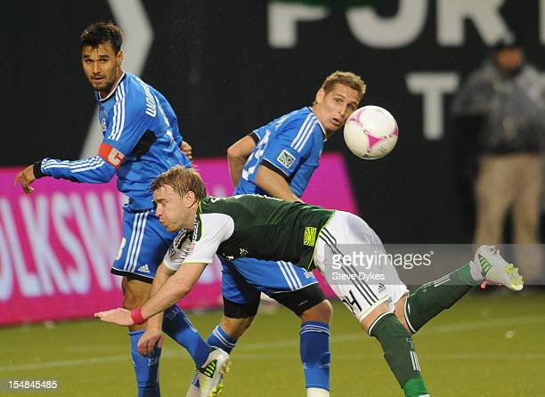 Chris Wondolowski of San Jose Earthquakes and Steven Smith of Portland Timbers go after a ball in front of the goal during the second half of the...