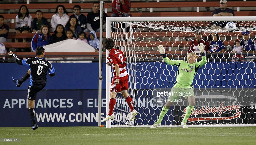 Chris Wondolowski of the San Jose Earthquakes shoots his second goal of the game past defenseman Zach Loyd and goalkeeper Kevin Hartman of FC Dallas...