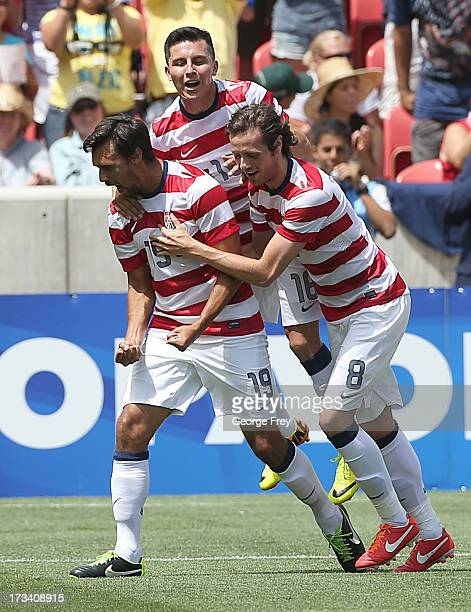 Chris Wondolowski of the United States celebrates his goal with his teammates Herculez Gomez and Jose Torres during a game against Cuba in the second...