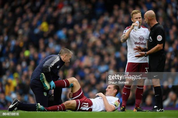 Chris Wood of Burnley is given treatment as he is injured during the Premier League match between Manchester City and Burnley at Etihad Stadium on...