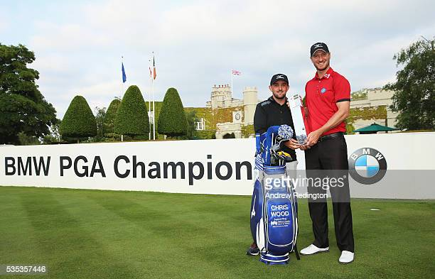 Chris Wood of England and caddie Mark Crane pose with the trophy following his victory during day four of the BMW PGA Championship at Wentworth on...