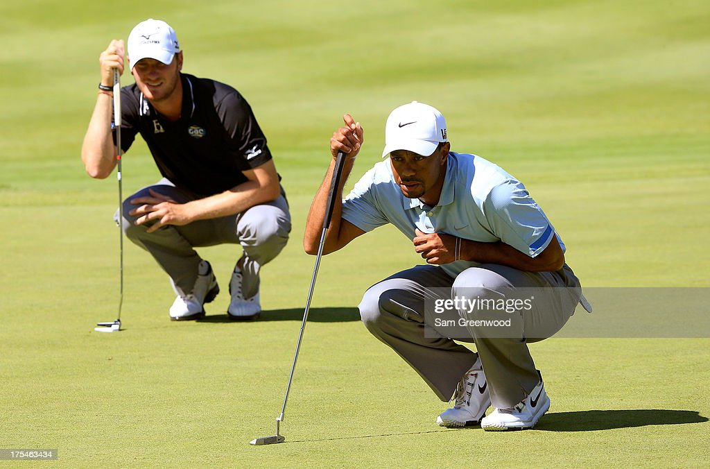 Chris Wood of England (L) and Tiger Woods line up putts on the 11th green during the Third Round of the World Golf Championships-Bridgestone Invitational at Firestone Country Club South Course on August 3, 2013 in Akron, Ohio.