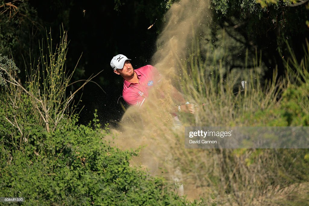 Chris Wood of England plays his second shot at the par 5 13th hole during the second round of the 2016 Omega Dubai Desert Classic on the Majlis...