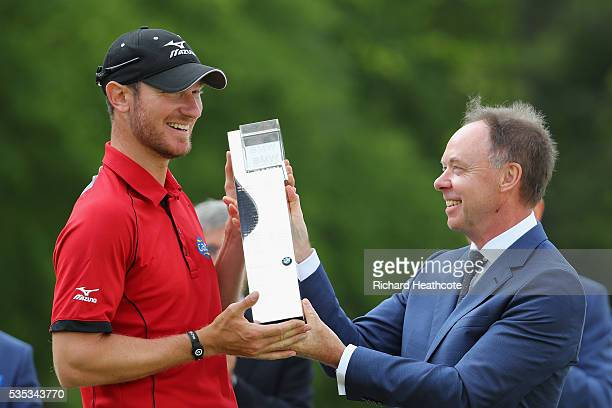 Chris Wood of England receives the trophy from Dr Ian Robertson Member of the Board BMW AG Sales following his victory during day four of the BMW PGA...