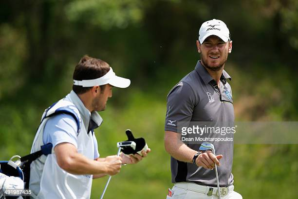 Chris Wood of England speaks to his caddie after he hits his second shot on the 1st hole during the final round of the Open de Espana held at PGA...
