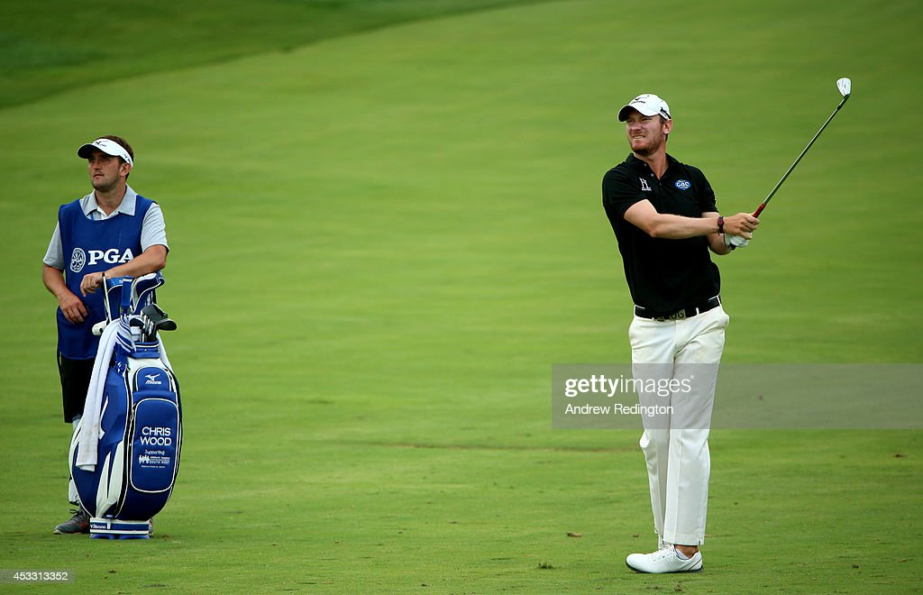 Chris Wood of England watches his approach shot on the ninth hole alongside his caddie Mark Crane during the first round of the 96th PGA Championship at Valhalla Golf Club on August 7, 2014 in Louisville, Kentucky.